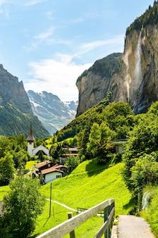 A igreja da vila e as cataratas de staubbach em lauterbrunnen - o cantão de berna, na suíça