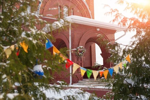 A igreja externa é feita de tijolos vermelhos, decorada com guirlandas e guirlandas de natal