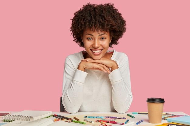 A ilustradora contente mantém as duas mãos embaixo do queixo, olha feliz para a câmera, faz esboços no bloco de notas, usa roupas casuais, bebe café para viagem, isolada sobre a parede rosa.