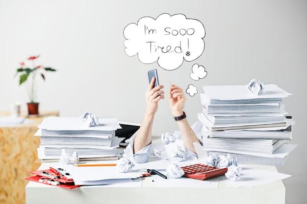 A imagem conceitual ou colagem sobre muitos dos papéis amassados na mesa de um local de trabalho masculino estressado