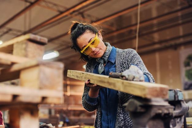 A imagem da meia-idade focalizou o carpinteiro fêmea que olha e que escolhe a madeira para seu trabalho em uma oficina.