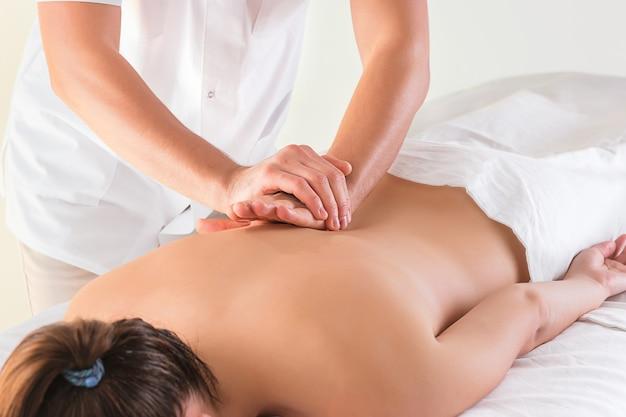 A imagem da mulher bonita no salão de massagem e mãos masculinas close-up