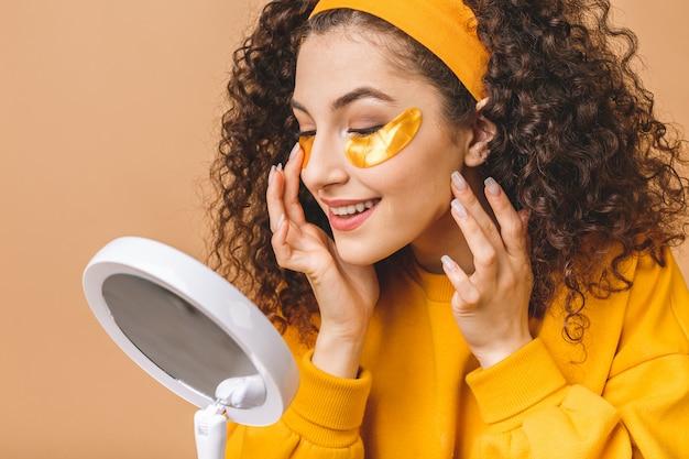 A imagem da mulher encaracolada bonita pura nova isolada sobre o fundo bege cuida de sua pele com tapa-olhos.
