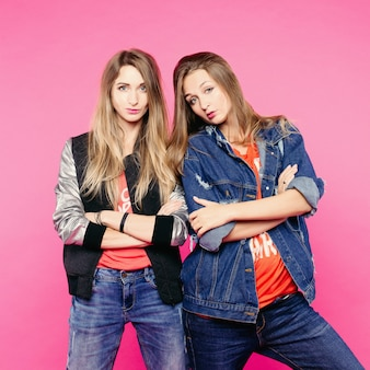 A imagem da primavera de duas mulheres positivas com óculos, amigas mulheres com cabelos lisos que abraçam. uma mulher com uma jaqueta jeans coloca os chifres de uma mulher. em roupas do estilo cotidiano e óculos.