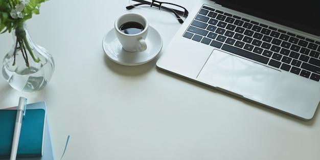 A imagem da vista superior da mesa de trabalho branca é circundada por uma xícara de café e equipamento de escritório.