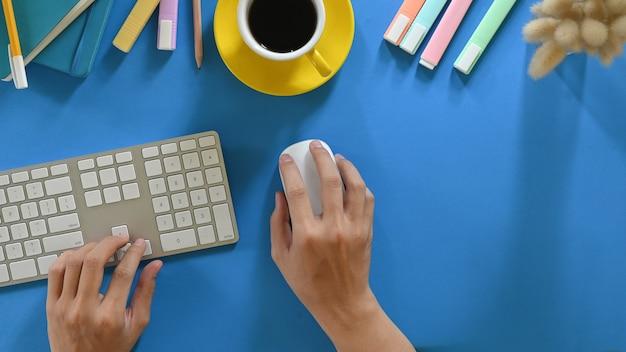 A imagem da vista superior das mãos está usando um teclado e mouse sem fio que colocam em uma mesa de trabalho colorida.