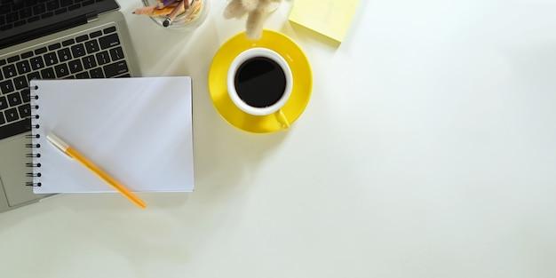 A imagem da vista superior de uma xícara de café está sobre uma mesa branca, cercada por equipamentos de escritório.