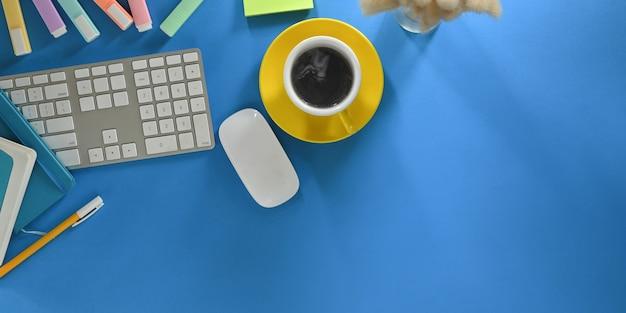 A imagem da vista superior de uma xícara de café está sobre uma mesa de trabalho colorida, cercada por equipamentos de escritório.