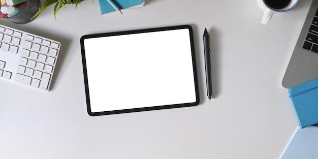 A imagem da vista superior do espaço de trabalho está cercada por um tablet de tela branca e equipamentos de escritório