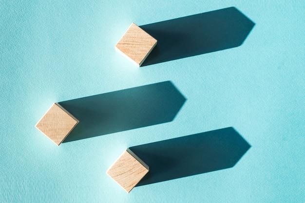 A imagem de três blocos de madeira com luzes fortes criam sombras profundas em uma superfície azul. conceito