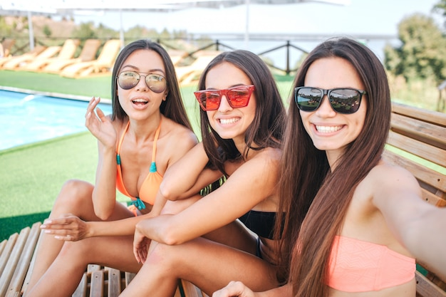 A imagem de três modelos senta-se em espreguiçadeiras e sorri. mulher à direita segura a câmera. outros dois são apenas pose. a mulher à esquerda parece espantada. todos eles usam óculos de sol.