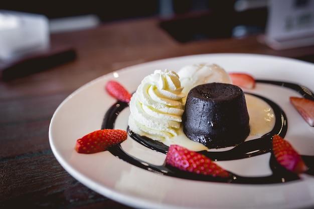 A imagem de um bolo de chocolate quente de lava com sorvete de baunilha e morango fresco