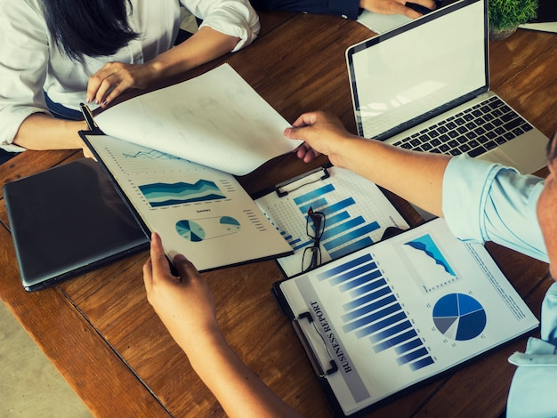 A imagem de um designer de negócios está segurando uma caneta para escrever um gráfico de renda de investimento bem-sucedido.