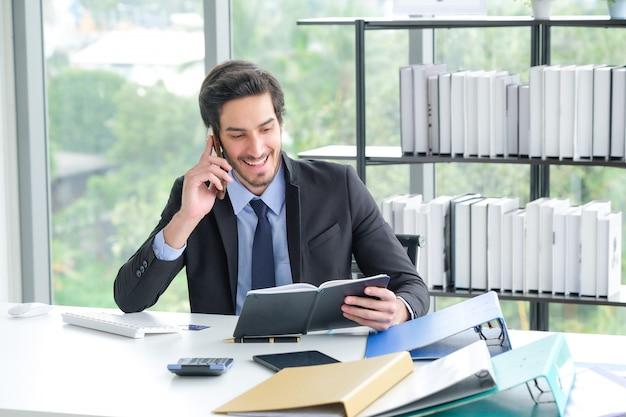 A imagem de um homem de negócios em uma mesa usando um telefone