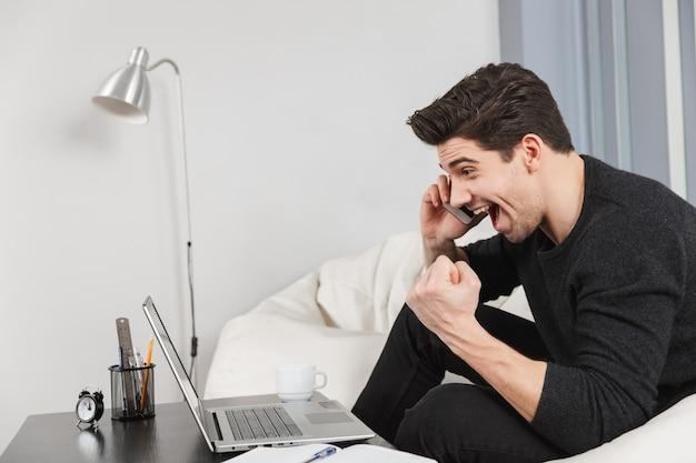 A imagem de um jovem bonito feliz em casa dentro de casa usando o computador laptop faz o gesto de vencedor falando pelo telefone celular.