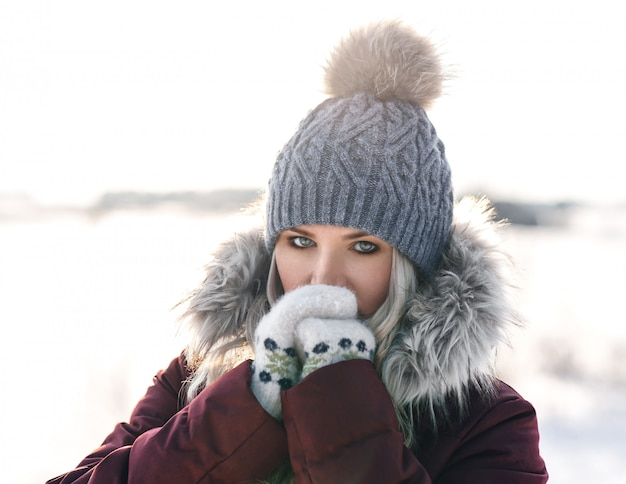 A imagem de uma garota com um chapéu de malha de inverno com pompom e luvas quentes aquece as mãos - respira nelas. imagem de uma menina que sente frio no inverno.