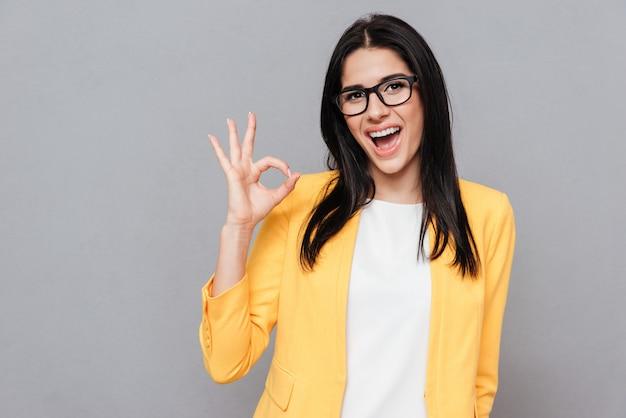A imagem de uma jovem alegre usando óculos e vestida com uma jaqueta amarela faz o gesto de ok sobre a superfície cinza. olhe para a frente.