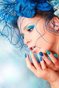 A imagem de uma jovem com maquiagem azul e manicure com design de unhas coloridas brilhantes de areia com enfeites brilhantes na cabeça.