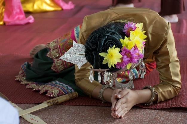 A imagem de uma menina asiática bonita que honra e que respeita após ter executado uma dança de espada.