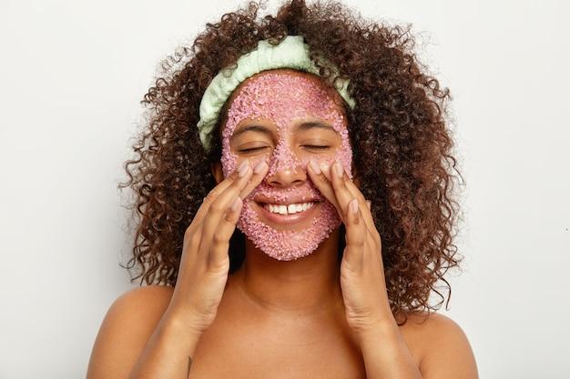 A imagem de uma mulher afro-americana bonita e feliz faz o peeling do rosto com esfoliante rosa sal marinho, toca as bochechas, fica com os ombros nus contra a parede branca. conceito de cuidados pessoais e beleza.