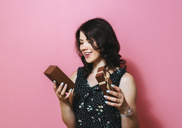 A imagem de uma mulher sorridente feliz abrindo uma caixa de presente e mostrando gestos isolados sobre parede rosa