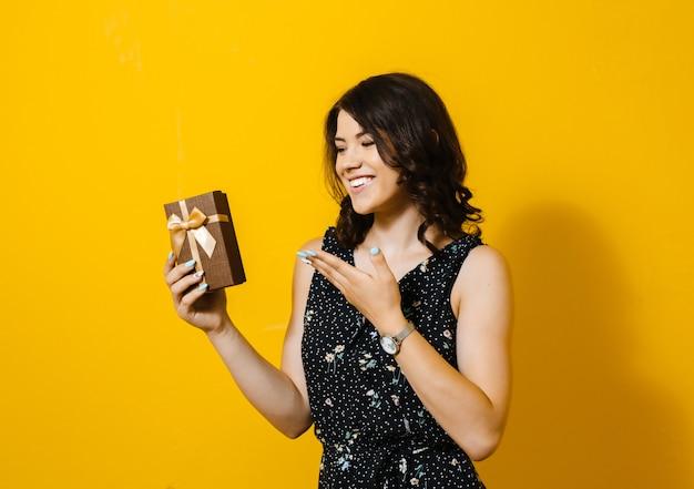 A imagem de uma mulher sorridente feliz abrindo uma caixa de presente e mostrando gestos isolados sobre uma parede amarela