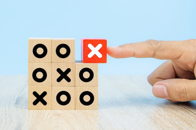A imagem do close-up do cubo escolhido a dedo deu forma a blocos de madeira do brinquedo com o símbolo x empilhado para a gestão de negócios e a estratégia aos conceitos do sucesso.