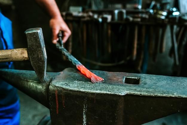 A imagem do close-up do ferreiro trabalha em uma oficina com um martelo e um ferro em brasa.