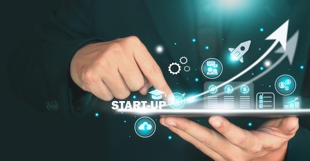 A imagem do conceito de start-up, businessan segurando o tablet e a interface digital da corporação empresarial. conceito de inicialização, conceito de negócio.