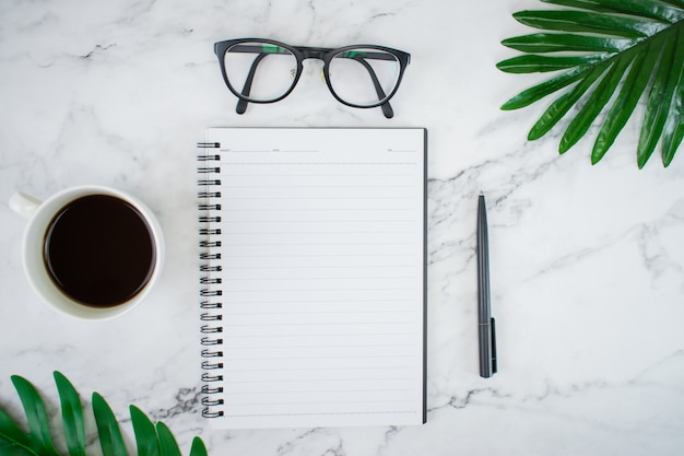 A imagem do espaço de trabalho com cadernos e acessórios, com folhas de palmeira sobre a mesa, padrão de mármore branco.
