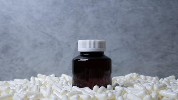 A imagem do frasco do medicamento e das cápsulas brancas para conteúdo científico ou médico.