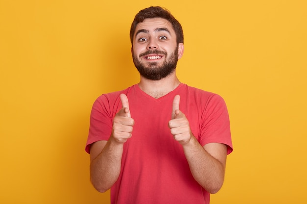A imagem do homem moderno de sorriso considerável veste a camisa ocasional vermelha de t que mostra o sinal aprovado com ambos os polegares, levantamento do modelo isolado no amarelo, homem novo farpado com expressão facial feliz.