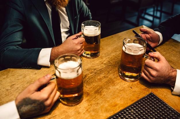 A imagem do manganês nos ternos senta-se na tabela. eles seguram canecas de cerveja e um telefone.
