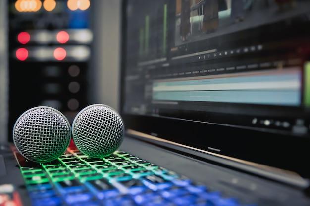 A imagem do microfone em close-up é colocada no notebook / laptop com o teclado de luz de fundo na sala de controle.