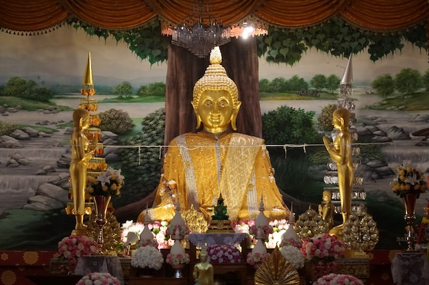 A imagem dourada de buddha do princípio em um templo.