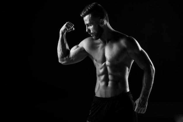 A imagem incolor do torso do construtor de corpo masculino atraente em fundo preto do estúdio.