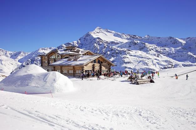 A inclinação em declive e os apres esquiam a cabana da montanha com o terraço do restaurante nos cumes italianos, europa, itália. área de esqui santa caterina valfurva