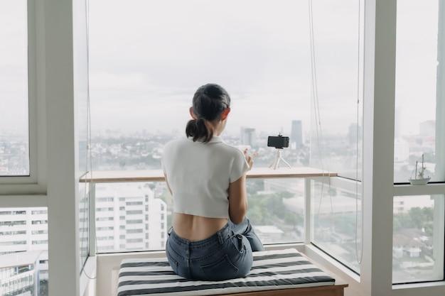A influenciadora feminina está gravando um clipe dela mesma com o smartphone