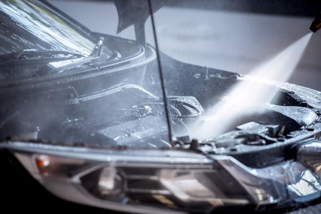 A injeção de lavar o motor enquanto lava o carro faz com que o motor brilhe e brilhe em preto.