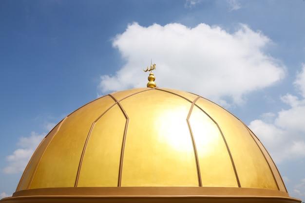 A inscrição allah na cúpula dourada da mesquita com o fundo do céu