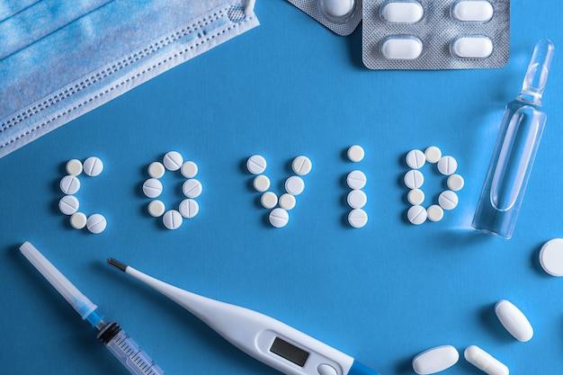 A inscrição covid, feita de tabletes redondos brancos. seringa descartável e medicamento em frasco em uma parede vermelha. vacina de coronavírus covid-19. espaço para texto