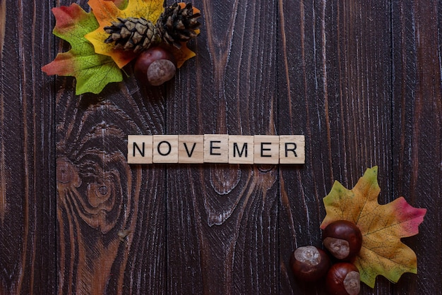 A inscrição das letras fica em um fundo de madeira palavra de outono no outono colorido embaçado