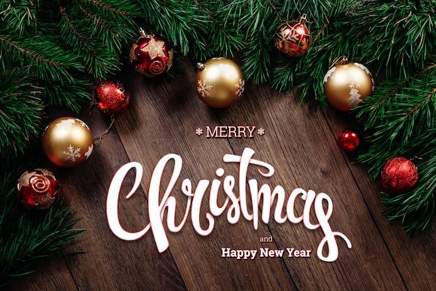 A inscrição de feliz natal, abeto vermelho verde e picar ramos em uma mesa de madeira marrom. cartão de natal, feriado. meios mistos.