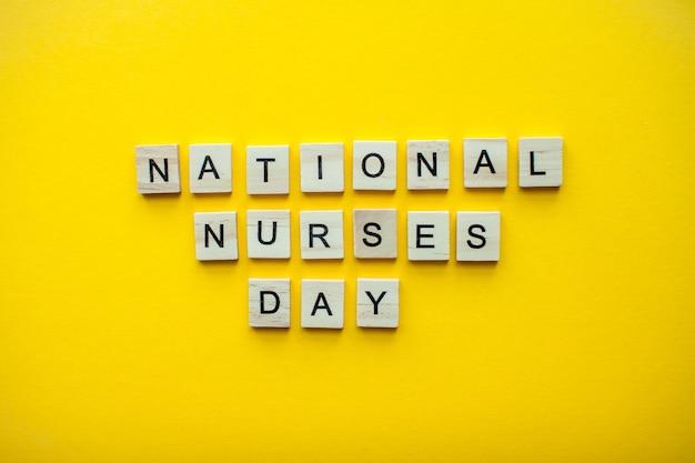 A inscrição do dia nacional das enfermeiras em blocos de madeira em um fundo amarelo brilhante.