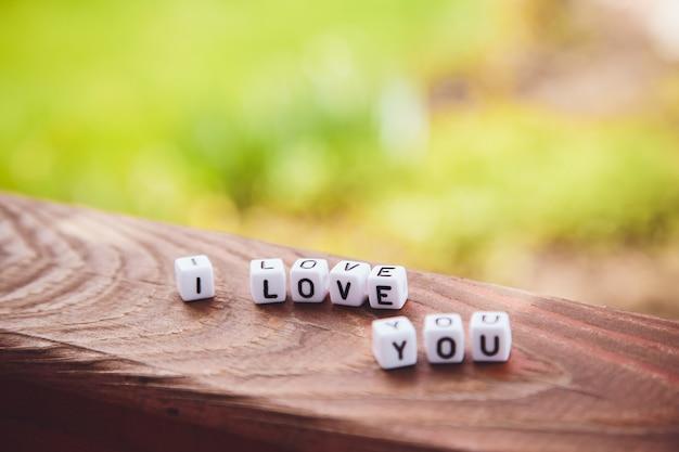 A inscrição dos cubos eu te amo em uma mesa de madeira