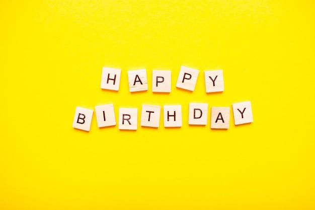 A inscrição feliz aniversário feita de blocos de madeira
