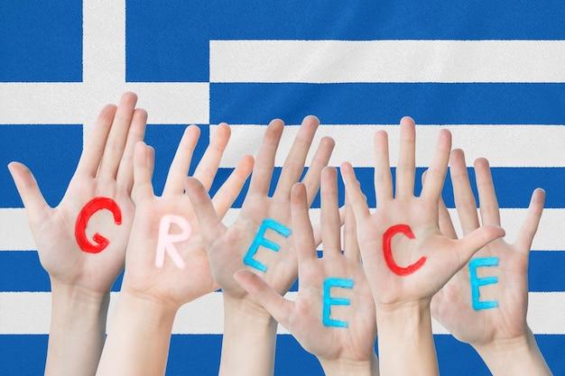 A inscrição grécia nas mãos das crianças contra a superfície de uma bandeira ondulante da grécia