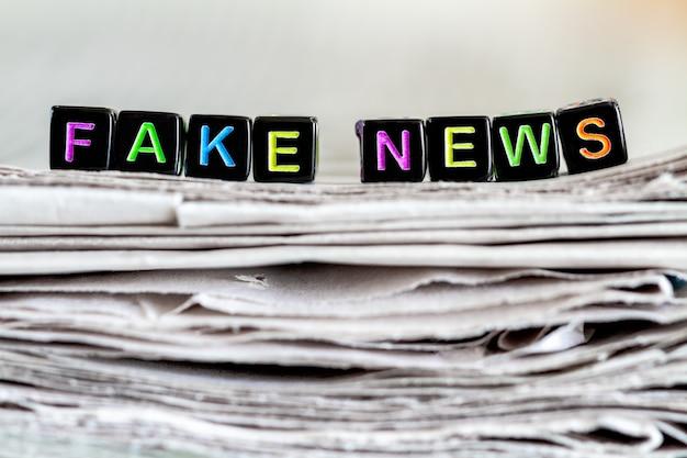 A inscrição notícias falsas na pilha de jornais.