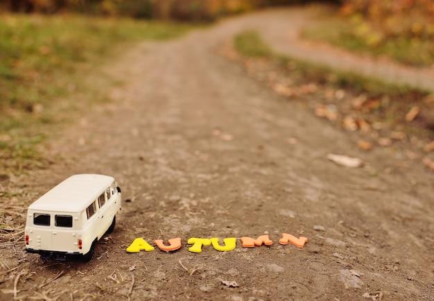A inscrição olá outono no fundo de um pequeno carro de brinquedo no fundo de árvores amarelas e parque