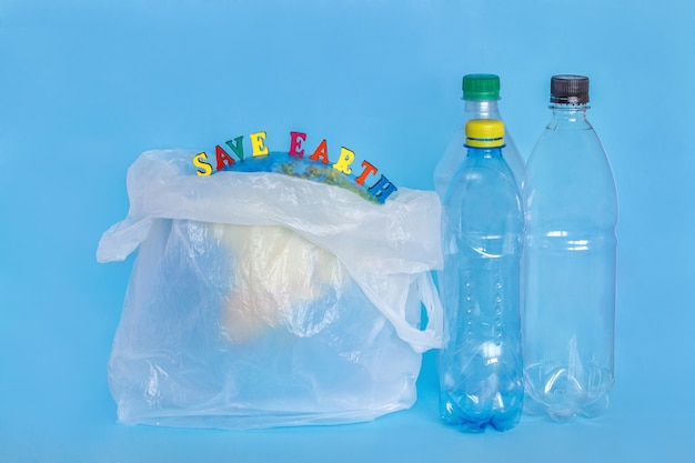 A inscrição salvar a terra, garrafas plásticas, terra abstrata no saco de polietileno, fundo azul.